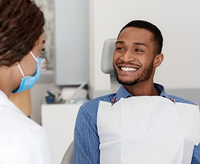 Man smiles at his K Street prosthodontist before treating cavities