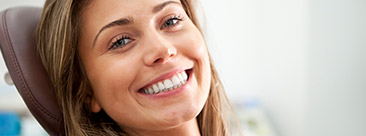Young woman with healthy smile in dental chair