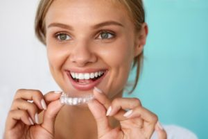 A woman smiling and holding a clear aligner.